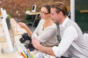éditeurs de photos occasionnels concentrés utilisant un ordinateur au bureau