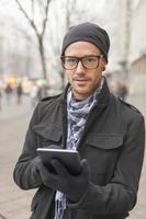 Man holdin i-pad tablet computer on street photo