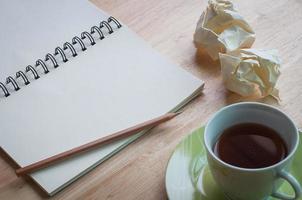 travaillant sur fond de bureau en bois avec une tasse de café photo
