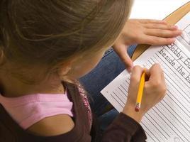 jeune fille au bureau à l'école sur blanc photo