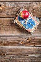 vieux livres et pomme sur le banc d'école photo