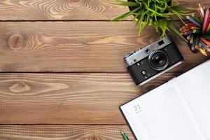 table de bureau avec caméra, fournitures et fleur photo