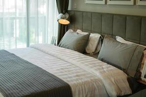 lampe de bureau en métal et oreiller gris sur le lit