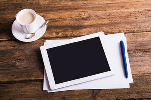 Tablette numérique et café sur fond de bois ancien