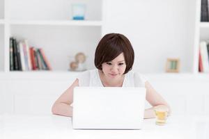 jeunes femmes pour faire fonctionner l'ordinateur personnel à la maison. photo