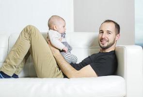 père avec bébé sur le canapé en prenant du bon temps