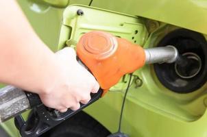 Les femmes détiennent une buse de carburant pour voiture à la station-service photo