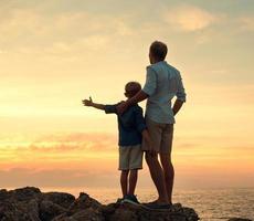 père et fils à la recherche sur le coucher du soleil à la mer photo