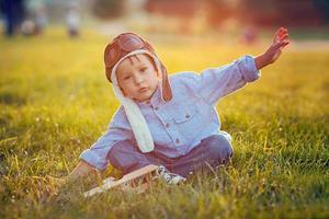 mignon garçon, jouer avec avion sur coucher de soleil dans le parc