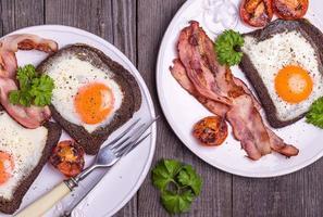 œufs frits dans du pain de seigle avec du bacon, dans un style rustique.