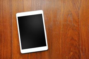 tablette blanche sur fond en bois.