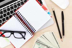 table de bureau avec pc, fournitures et argent comptant