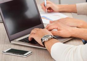 main d'homme d'affaires travaillant avec un ordinateur portable au bureau photo