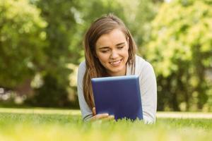 étudiant universitaire souriant couché et à l'aide de tablet pc photo