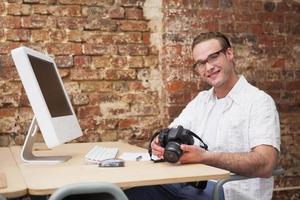 homme souriant, tenant un appareil photo