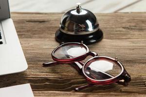 l'ordinateur portable, du papier vierge, des lunettes et une petite cloche sur le photo