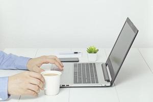 homme travaillant sur ordinateur portable. pause café au bureau.