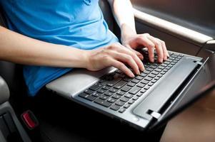 femme d'affaires méconnaissable assis dans la voiture avec un ordinateur portable sur ses genoux photo