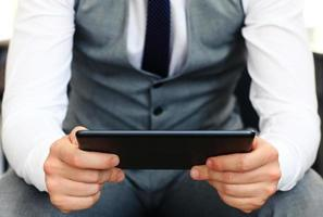 jeune adulte travaillant sur une tablette numérique.
