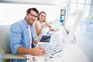deux éditeurs photo heureux travaillant avec des planches contact