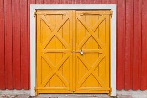 Porte en bois jaune verrouillée dans le mur rouge, fond photo