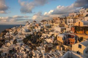 ville blanche sur la pente de la colline, coucher de soleil, oia, santorin, grèce photo