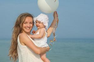heureuse belle mère et fille profitant du temps à la plage photo