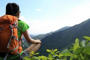 Backpacker femme profiter de la vue sur la falaise de pic de montagne