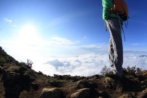 jambes de randonneur sur le sommet de la montagne au coucher du soleil profiter de la vue photo
