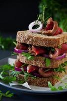 sandwich au pain aux céréales avec rôti de boeuf, oignon et roquette.