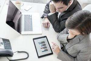 partenaires commerciaux masculins et féminins analysant les statistiques annuelles r photo