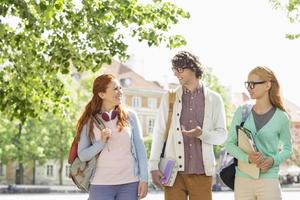 jeunes étudiants discutant en marchant dans la rue photo