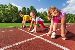 trois enfants souriants en position prête à courir