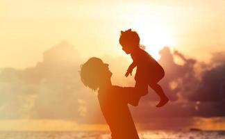 père et petite fille silhouettes au coucher du soleil photo