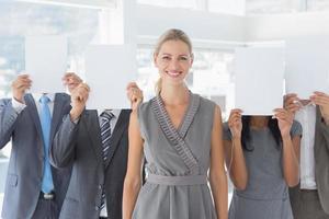 collègues de travail se cachant le visage avec du papier photo