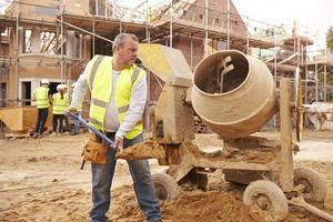 travailleur de la construction sur le chantier de mélange de ciment photo