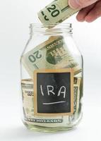 main, insertion d'argent dans un pot d'épargne ou une banque photo