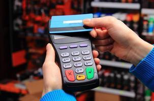 Main de femme payant avec carte de crédit sans contact, technologie NFC photo