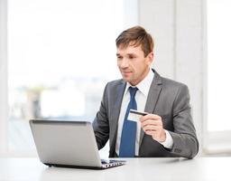 homme avec ordinateur portable et carte de crédit au bureau