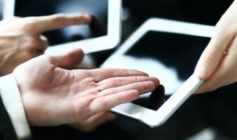 les gens d'affaires faisant des affaires, en cours de démonstration sur le pavé tactile photo