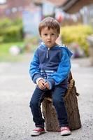 portrait d'un garçon, assis sur un tronc d'arbre photo
