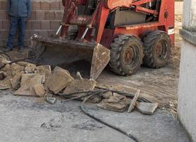Travailleur d'équipe retrait de l'ancien revêtement de sol avec mini-pelle photo