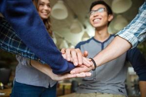 des collègues heureux se mettent la main les uns sur les autres photo