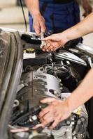 mécanicien automobile passant une clé à un collègue photo