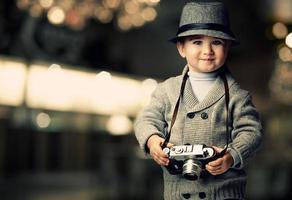 petit garçon avec appareil photo rétro sur fond flou.