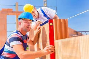 Les travailleurs de chantier de construction vérifiant l'enveloppe du bâtiment photo