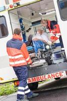 ambulanciers paramédicaux mettant le patient en ambulance photo