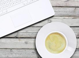ordinateur portable et une tasse de café avec de la crème photo
