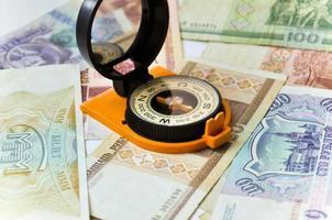 billets de banque et boussole. navigation dans le monde de la finance. photo