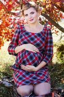 fille enceinte porte une robe à carreaux dans le parc